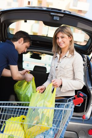 young couple arranging shopping bags in car Stock Photo