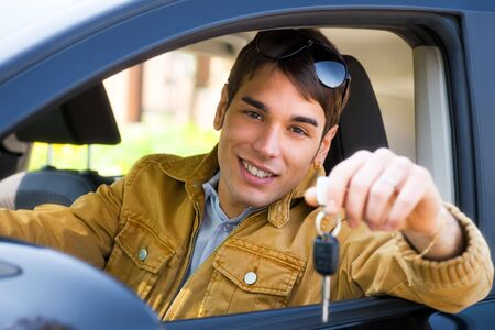 young man sitting inside car showing keys to new car Stock Photo - 4685657