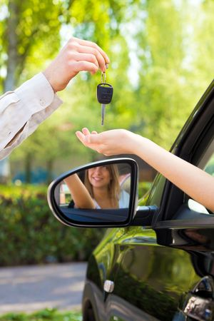 close up of female with arm outstretched taking car keys from man. Copy space Stock Photo - 4692731