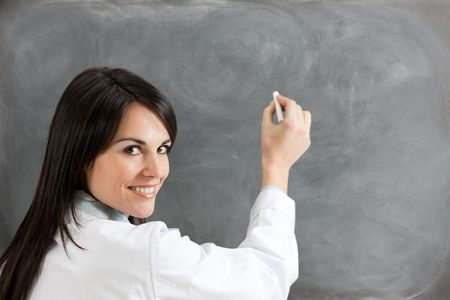copy writing: rear view of female teacher in lab clothes holding chalk against blank blackboard. Copy space