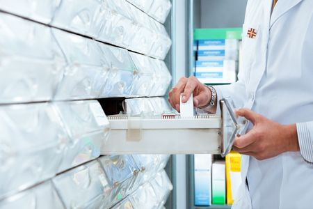 pharmacist: cropped view of pharmacist taking medicine from drawer. Copy space