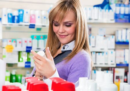 Portrait of blonde woman doing shopping in pharmacy. Stock Photo - 4694776