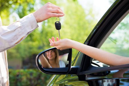 car keys: close up of female with arm outstretched taking car keys from man. Copy space
