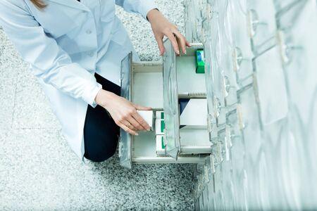 knees bent: elevato angolo di visione di farmacista tenendo medicina cassetto. Copia spazio Archivio Fotografico