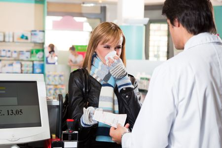handing: sick woman giving prescription to pharmacist