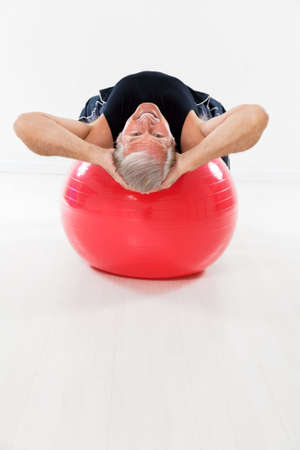 senior man working out on fitness ball and looking at camera. Copy space photo