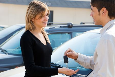 car keys: cropped view of man in car dealership giving car keys to client