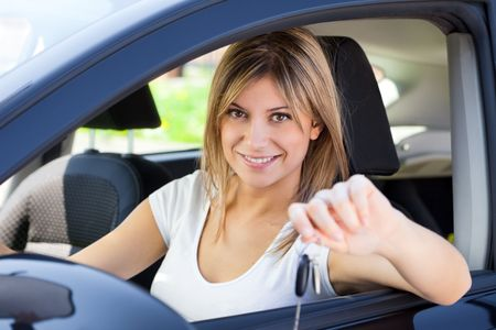 young man sitting inside car showing keys to new car Stock Photo