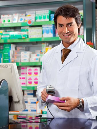 portrait of mid adult pharmacist scanning medicine with barcode reader photo