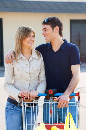 portrait of young couple pushing shopping cart outdoors photo