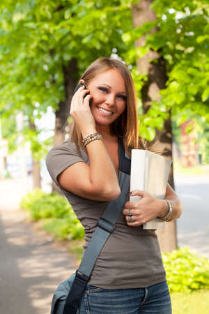 female college student talking on the phone outdoors photo