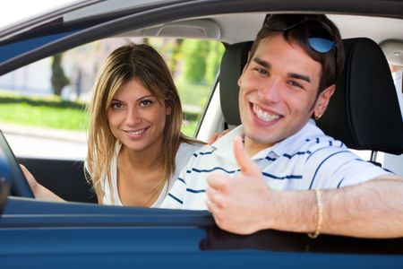 young couple in car showing thumbs up photo
