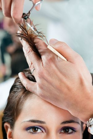 coiffeur: Close up of young woman having her hair being cut. Narrow focus on hand and hair