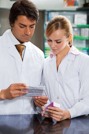 portrait of two pharmacists reading directions of medicine photo