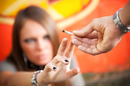 substance abuse: cropped view of two young adults smoking a joint
