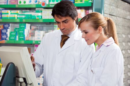 pharmacist: portrait of two pharmacists looking at computer monitor Stock Photo
