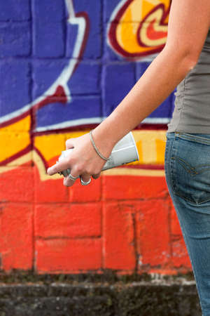 close up of young graffiti artist holding spray can. Copy space photo
