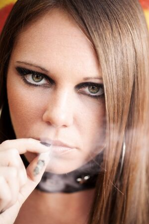 portrait of young female smoking a joint.  photo
