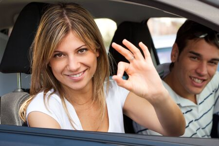 young couple in car showing okay sign