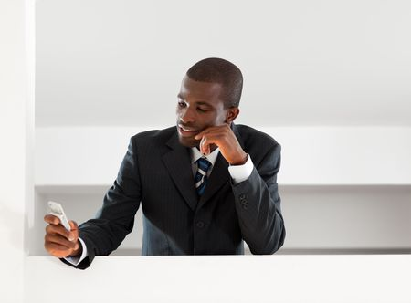 young adult afro-american businessman reading emails on his smartphone indoors. Copy space photo