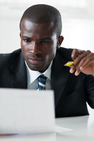 young adult afro-american businessman examining documents indoors Stock Photo - 4837370