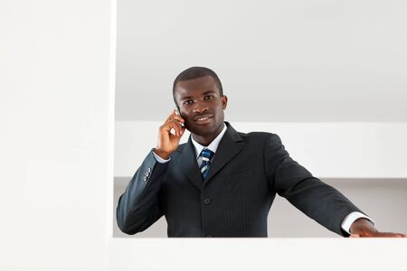 young adult afro-american businessman talking on the phone indoors. Copy space photo