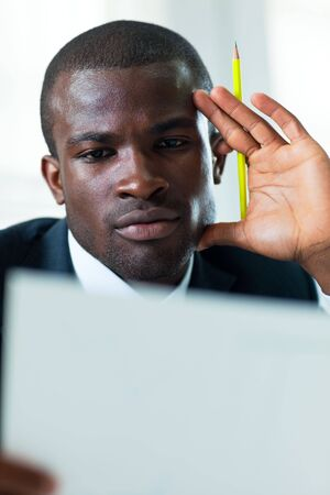 young adult afro-american businessman examining documents indoors Stock Photo - 4852268