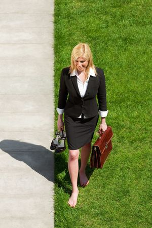 barefoot women: high angle view of mid adult businesswoman walking barefoot on grass
