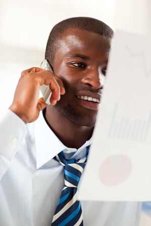 young adult afro-american businessman examining charts and talking on the phone photo