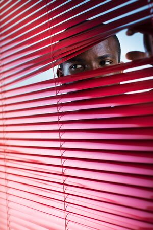 paranoid: afro-american businessman glancing through red blinds. Copy space