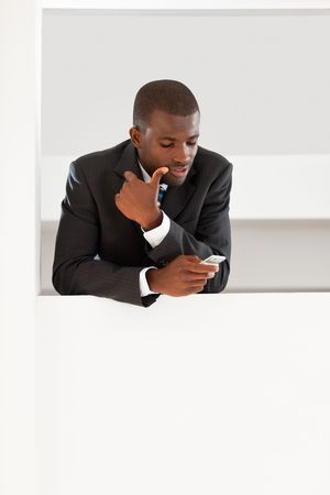 young adult afro-american businessman reading emails on his smartphone indoors. Copy space Stock Photo - 4884025