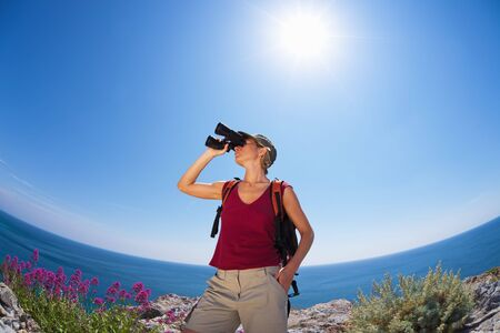 bird watcher: young blonde woman hiking watching through binoculars. Copy space