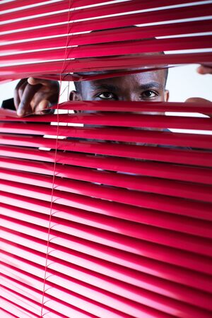 glancing: afro-american businessman glancing through red blinds. Copy space