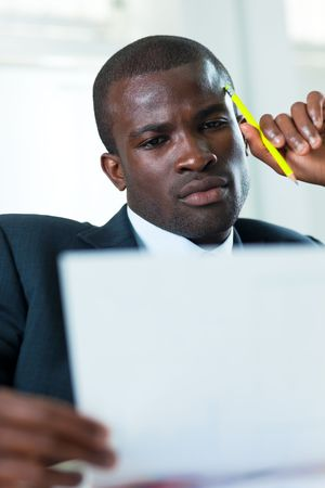 young adult afro-american businessman examining documents indoors photo