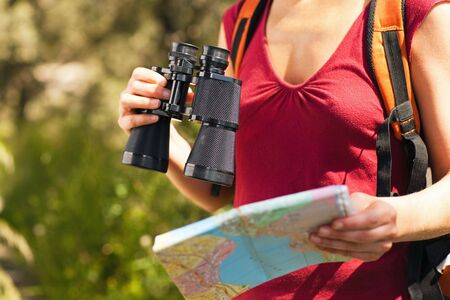 bird watcher: cropped view of female bird watcher holding binoculars and map.