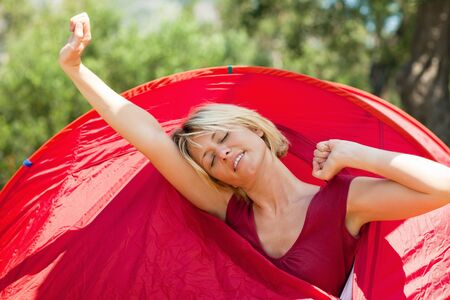 blonde woman in tent waking up and stretching arms. photo