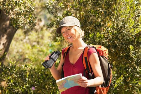 bird watcher: young blonde woman hiking and holding binoculars and map.
