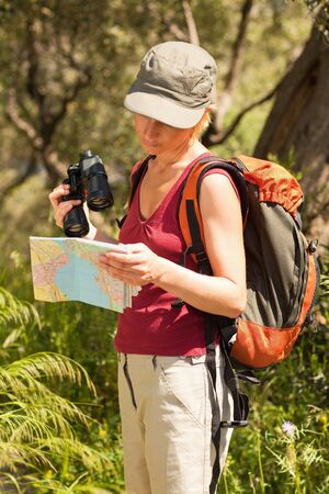 bird watcher: young blonde woman hiking and reading map.