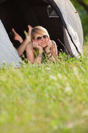 young blonde woman lying in tent with feet crossed. Copy space photo