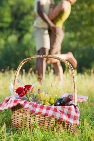 portrait of young multiethnic couple picnicking in park photo