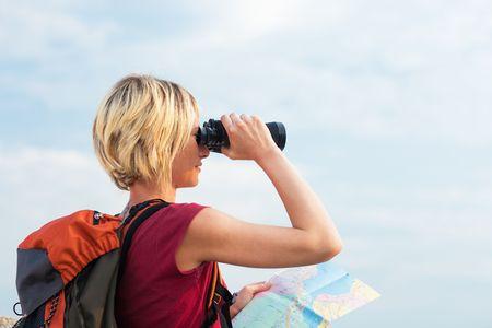 young blonde woman hiking watching through binoculars. Copy space
