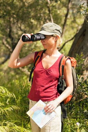 young blonde woman hiking and holding binoculars and map. photo