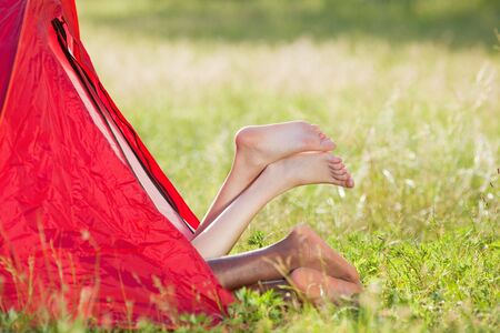 feet crossed: young multiethnic couple lying in tent with feet crossed. Copy space Stock Photo