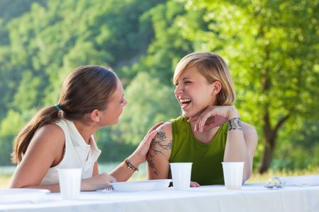 weekend activities: two female friends having picnic outdoors and laughing Stock Photo