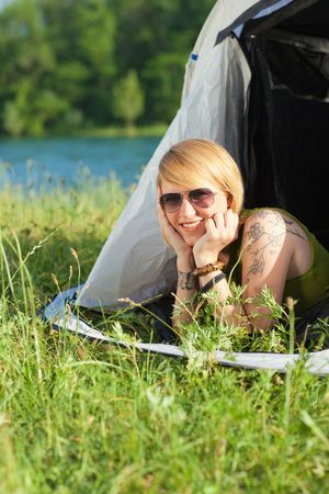 young blonde woman lying in tent and looking at camera. Copy space photo