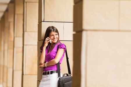 portrait of young adult businesswoman talking on the phone and leaning on column. photo
