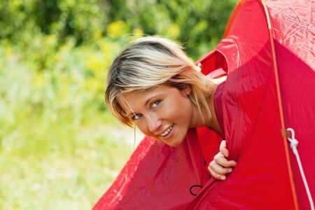 young blonde woman going out from tent and looking at camera. Copy space photo