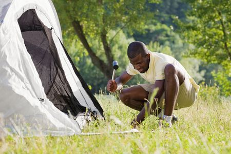 knees bent: Young afro-american man fastening tent and holding hammer