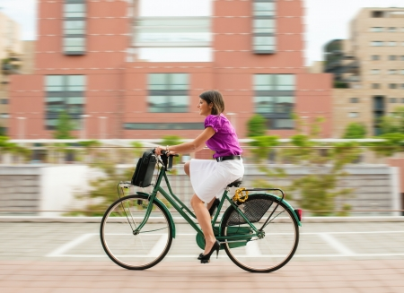 working attire: mixed-race businesswoman going to work by bike.