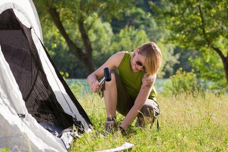 knees bent: Giovane donna di fissaggio tenda e martello azienda Archivio Fotografico
